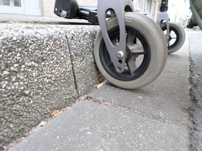 Ein Rollstuhl steht vor einer Stufe (Barriere)